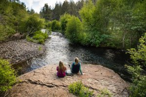 Two hikers take a break next to Whychus Creek at Whychus Canyon Preserve. By Tyler Roemer