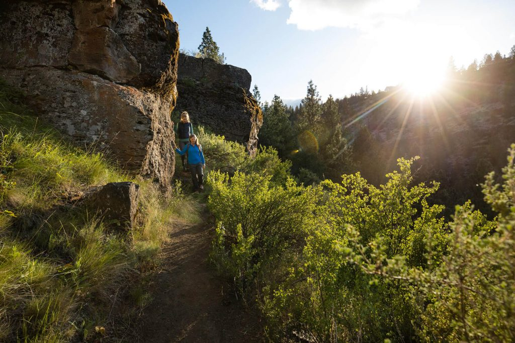 Hikers walk down the trail into Whychus Canyon at sunset. By Tyler Roemer