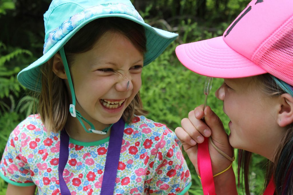 Lucy Egertson looks at Zoe Mowry with a butterfly on her nose. By Deschutes Land Trust